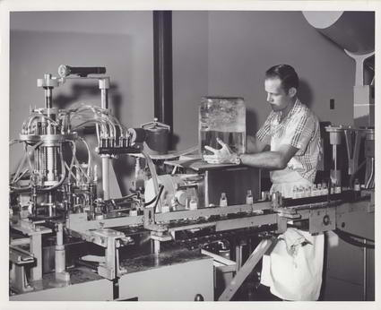 An employee working with equipment at Adams Extract Company (Austin History Center, Austin Public Library)