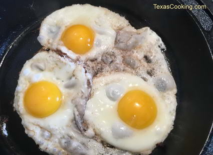 Fried eggs in a cast-iron skillet.